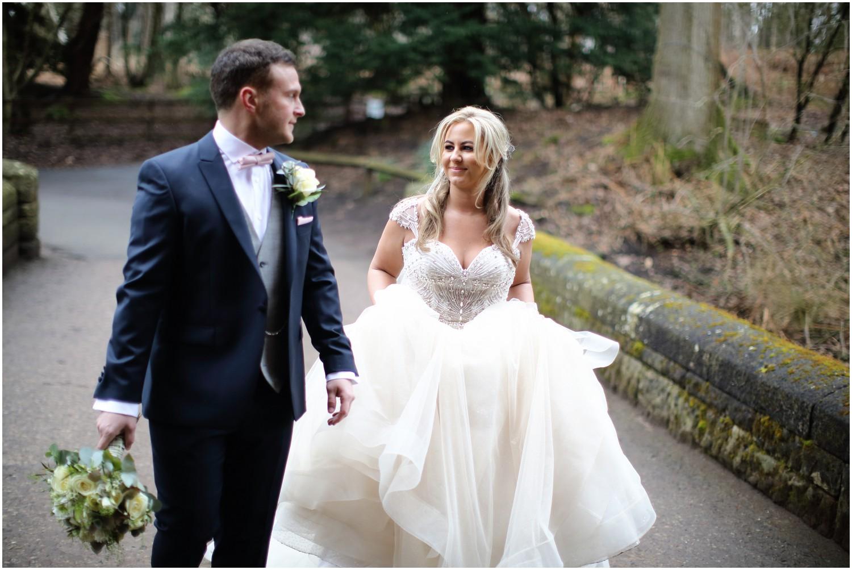 bride and groom walking bride holding onto dress
