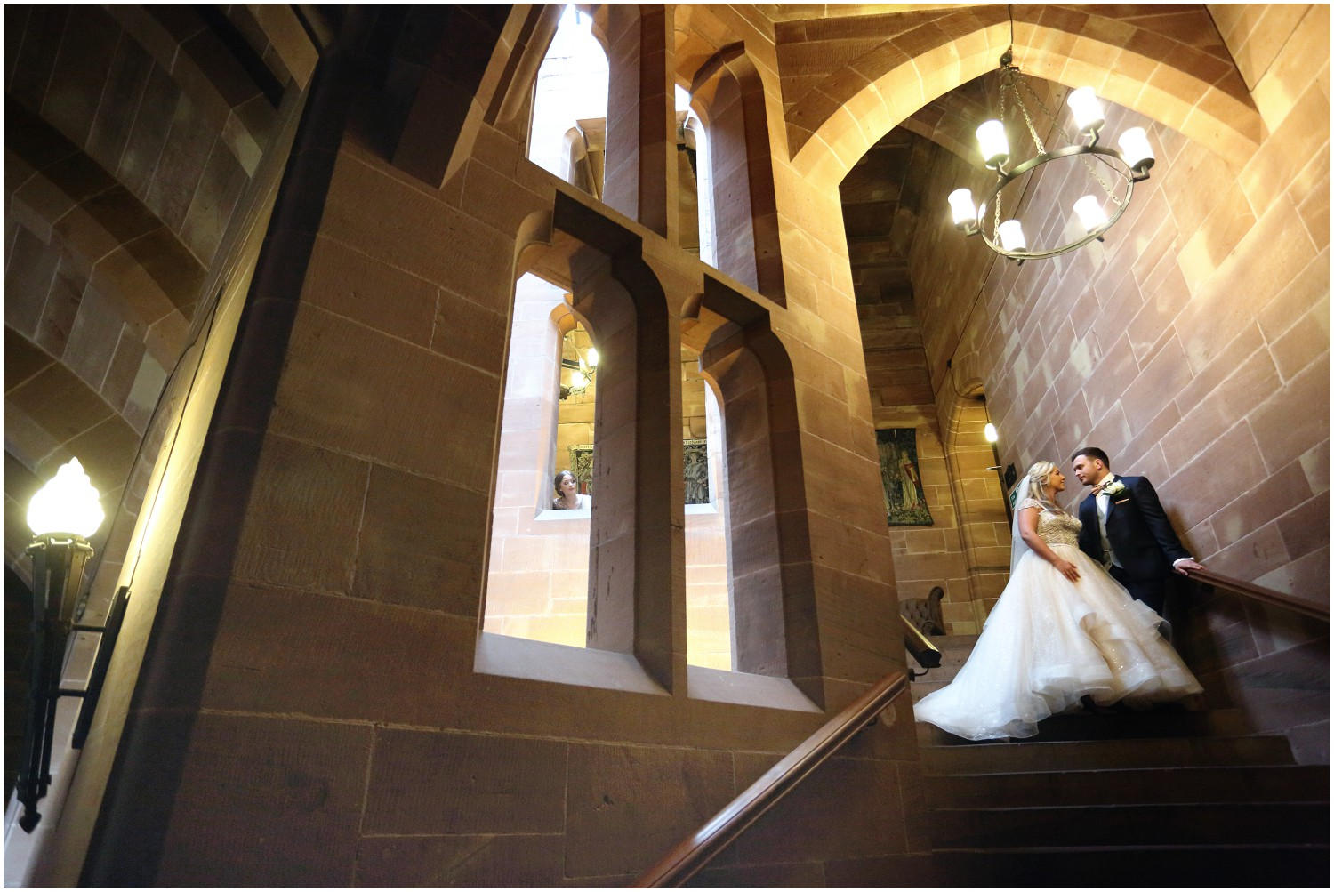 bride and groom on staircase at castle