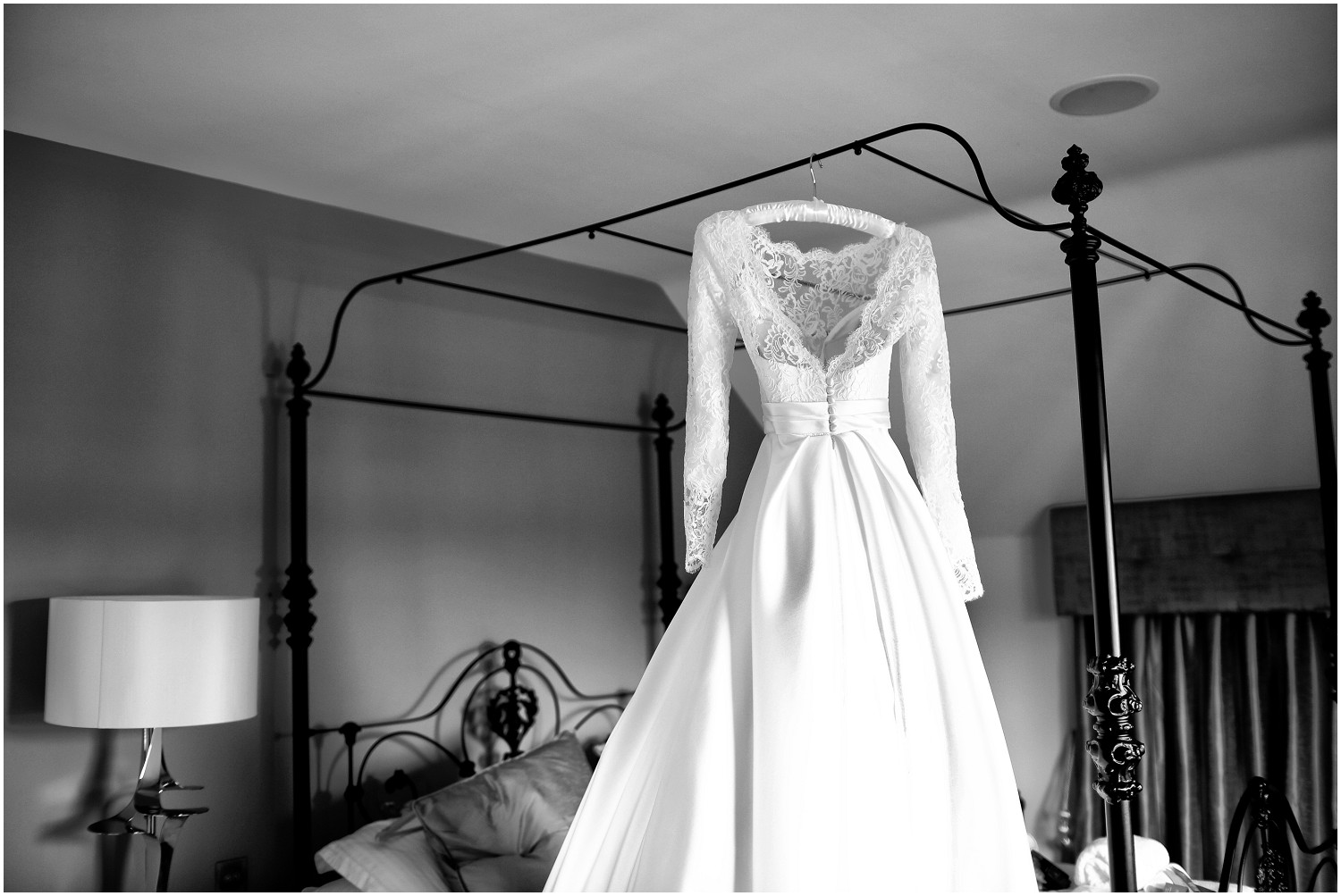 wedding dress hanging from bed