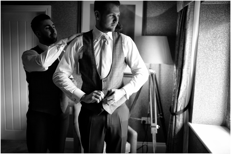 groom putting on waistcoat
