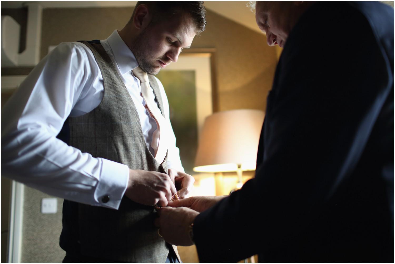 groom fastening waistcoat