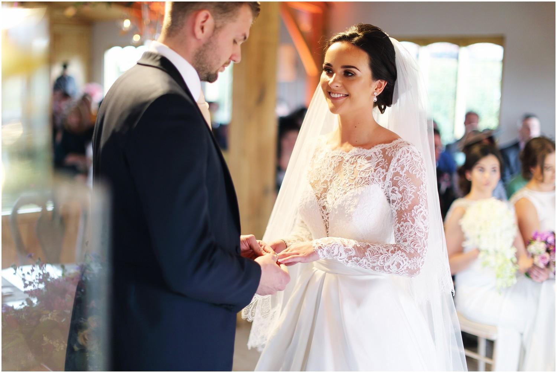 groom putting brides wedding ring on