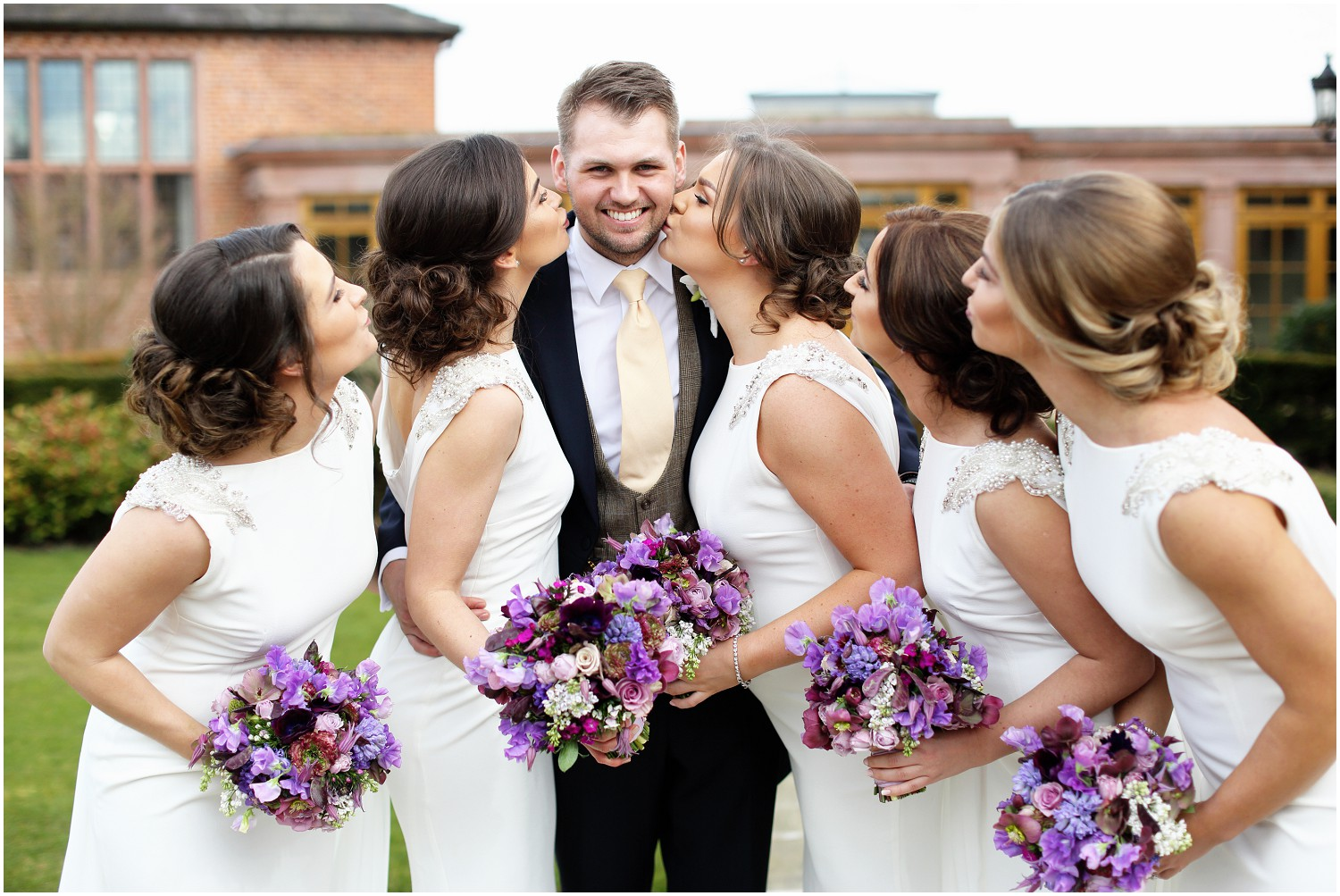 bridesmaids kissing groom