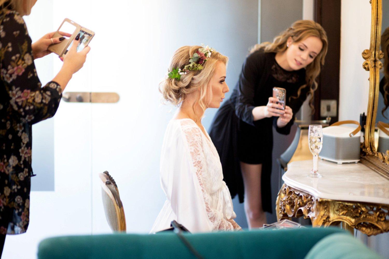 mua taking brides photograph