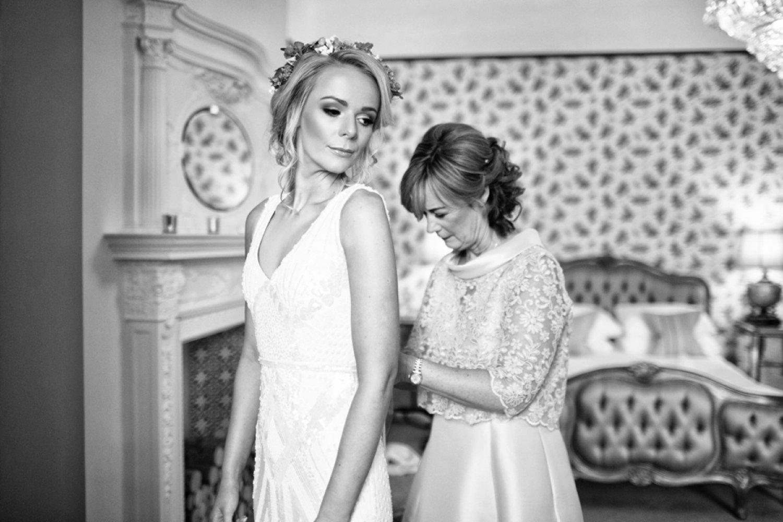 mum fastening bride into dress