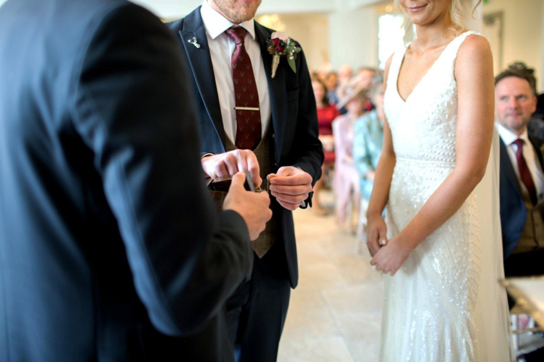 groom taking wedding ring from bestman