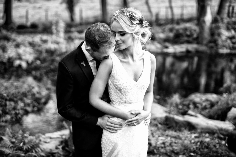 groom kissing brides shoulder