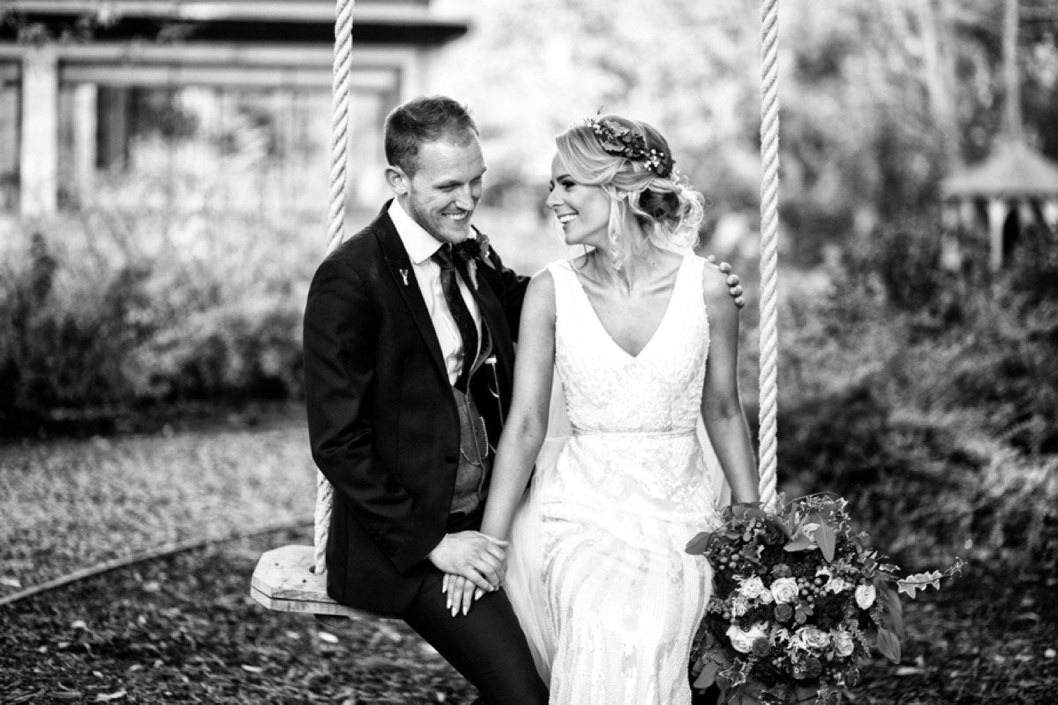 bride and groom laughing on tree swing