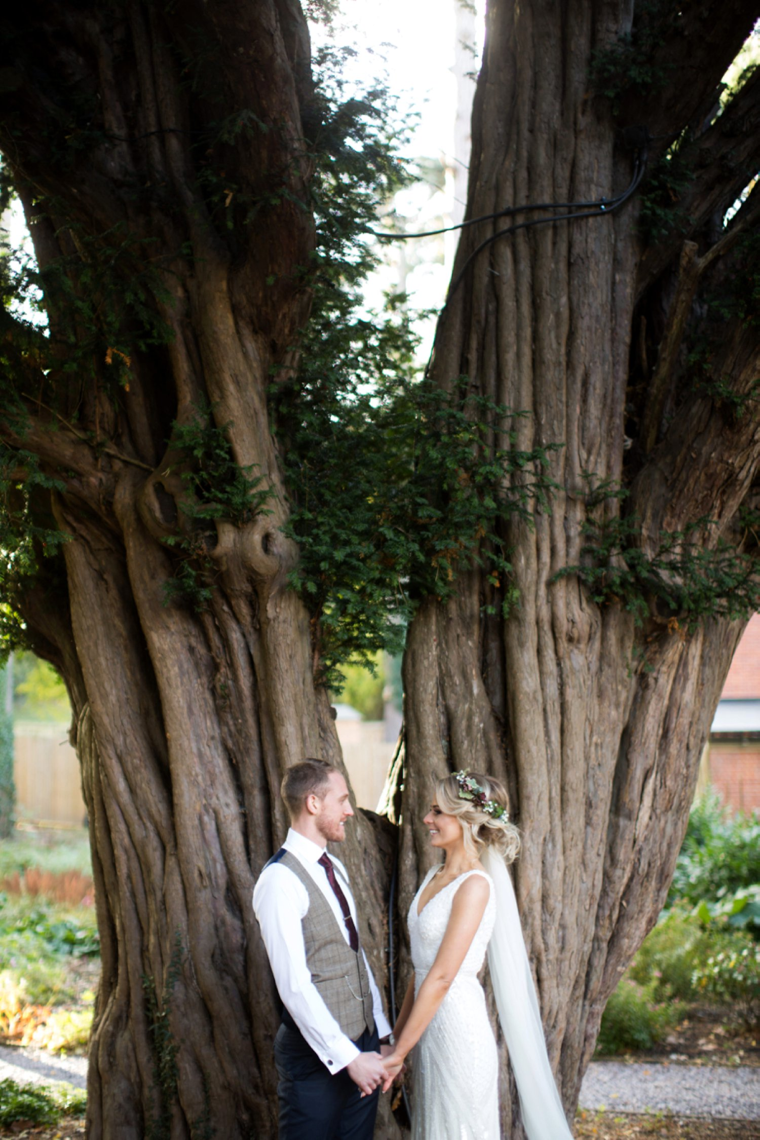 bride and groom holding hands by yew tree