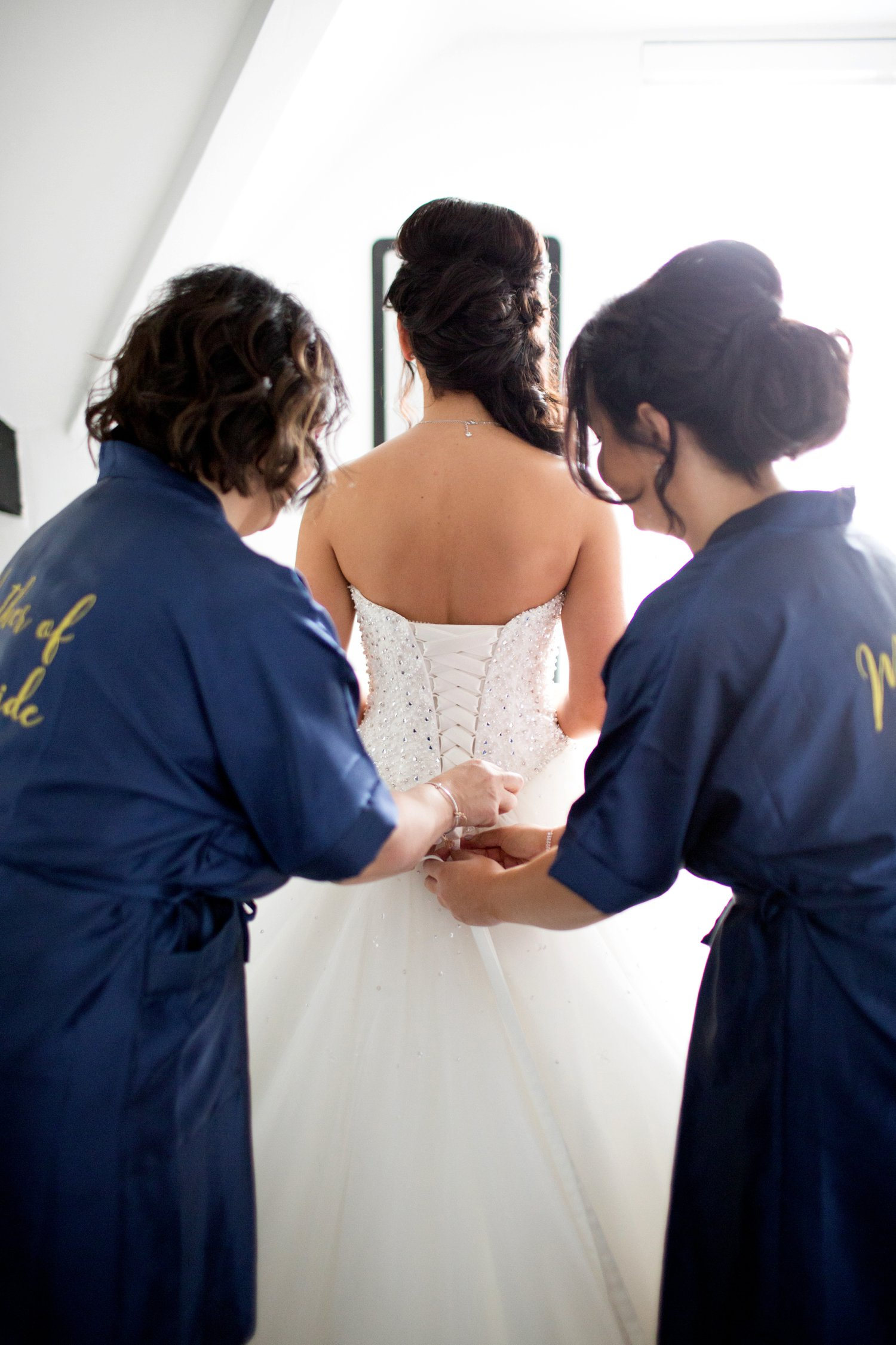 bride being laced into wedding dress